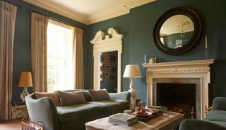 Elegant living room with fireplace, light shining in the window onto the dusky blue interior.